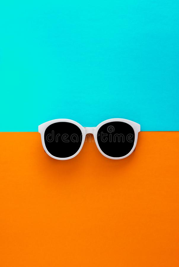 Sunny stylish white sunglasses on a bright blue-cyan and yellow-orange background, top view, isolated. Copy space. Flat lay.  stock photos