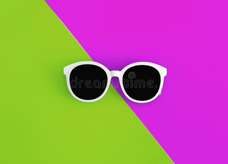 Sunny stylish white sunglasses on a bright green-cyan and crimson-pink background, top view, isolated. Copy space. Flat lay.  stock photography