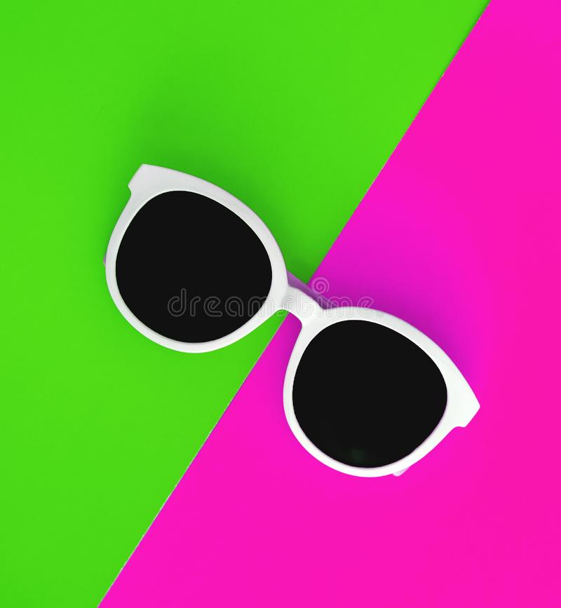 Sunny stylish white sunglasses on a bright green-cyan and crimson-pink background, top view, isolated. Copy space. Flat lay.  royalty free stock photography