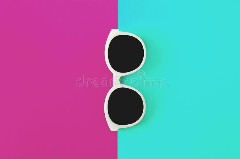 Sunny stylish white sunglasses on a bright green-cyan and crimson-pink background, top view, isolated. Copy space. Flat lay.  royalty free stock images