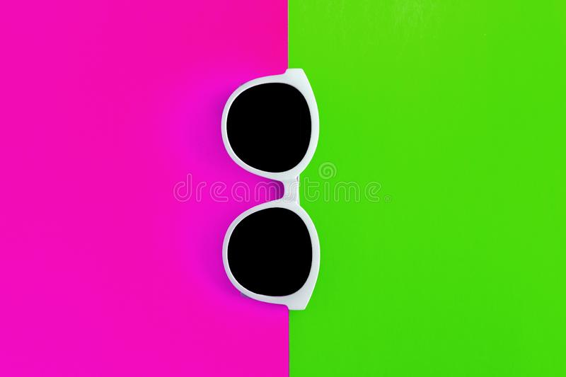 Sunny stylish white sunglasses on a bright green-cyan and crimson-pink background, top view, isolated. Copy space. Flat lay.  royalty free stock photos