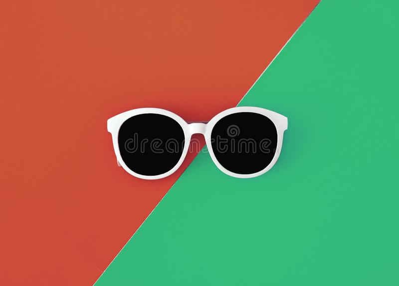 Sunny stylish white sunglasses on a bright green-cyan and red-orange background, top view, isolated. Copy space. Flat lay.  royalty free stock image