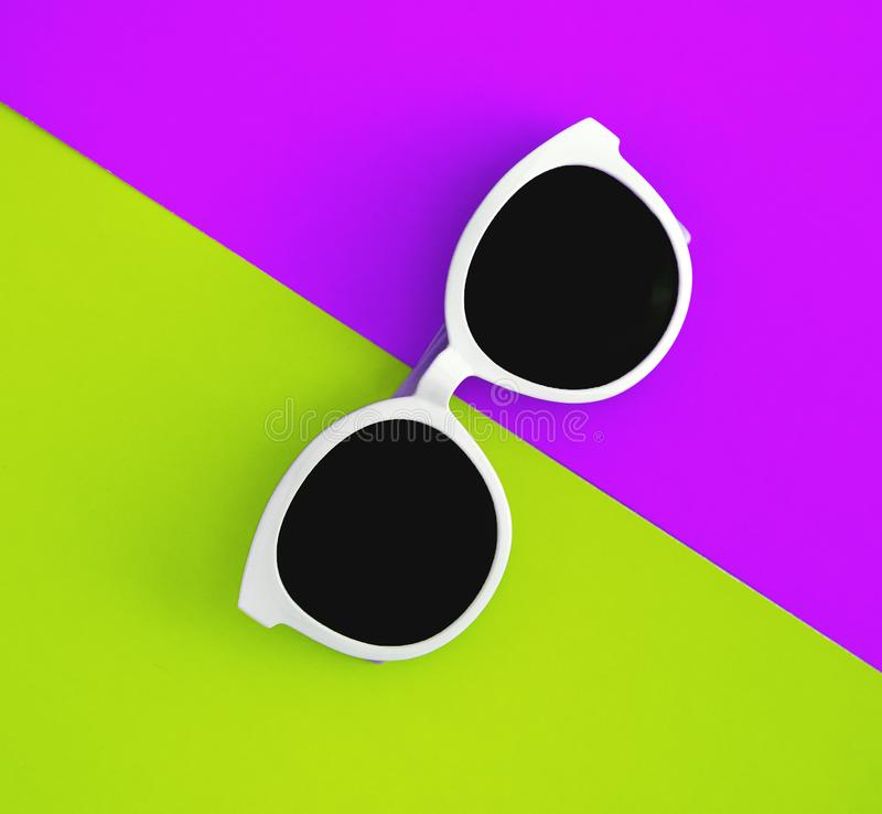 Sunny stylish white sunglasses on a bright purple-lilac and yellow-green background, top view, isolated. Copy space. Flat lay.  stock photography