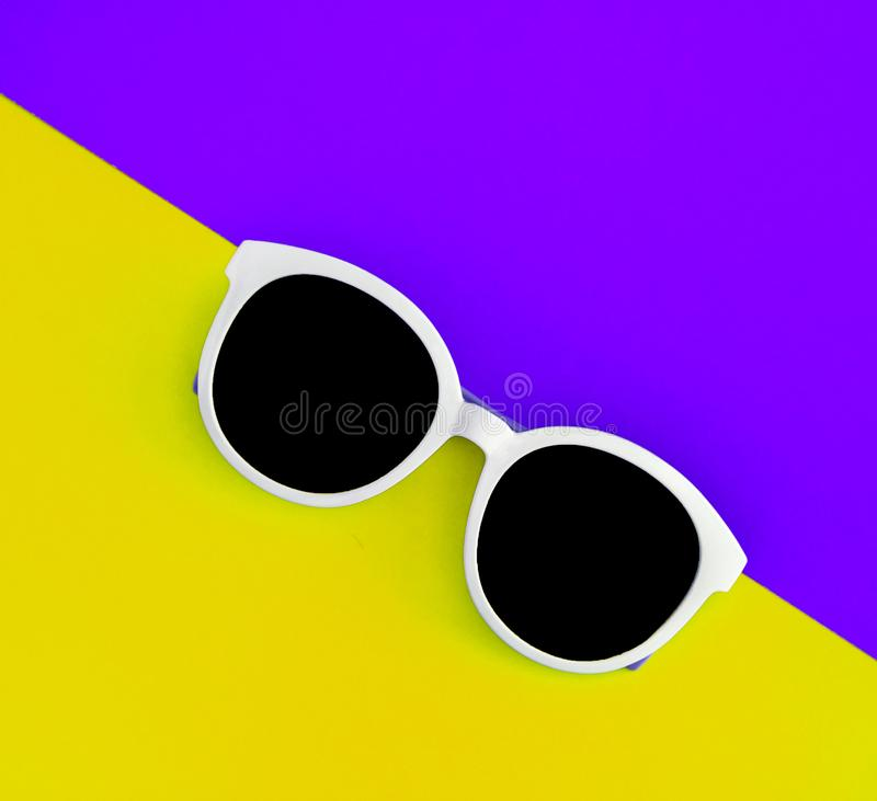 Sunny stylish white sunglasses on a bright purple-lilac and yellow-orange background, top view, isolated. Copy space. Flat lay.  stock images