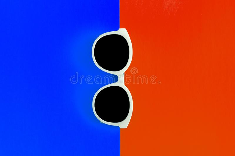 Sunny stylish white sunglasses on a bright red and blue background, top view, isolated. Copy space. Flat lay.  stock photos