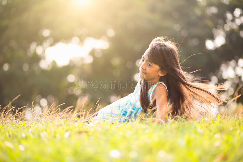 Sunny summer day. Cute little asian girl laying in the grass on a sunny summer day, Outdoor portrait royalty free stock images