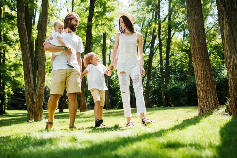 Sunny summer day. Happy young family dressed in the white casual clothes walks in the park. stock photo
