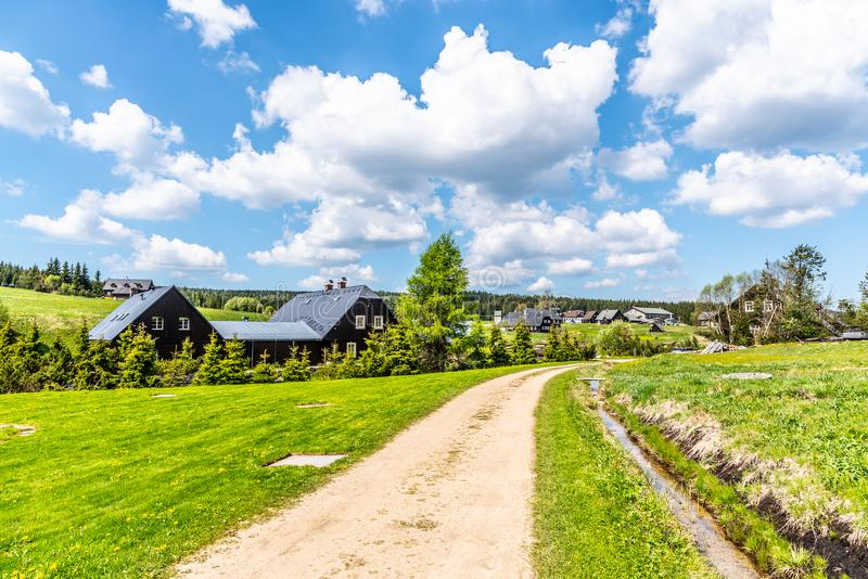 Sunny summer day in Jizerka mountain village. Dusty country road, green meadows and blue sky with white clouds, Jizera stock photo