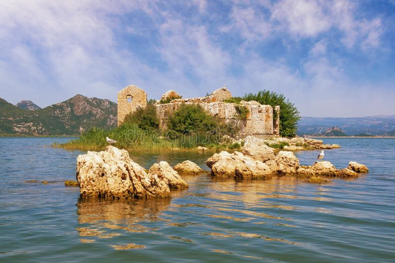 Sunny summer day. Picturesque lake with ruined fort on small island. View of National Park Lake Skadar. Montenegro. Sunny summer day. Picturesque lake with a stock photo