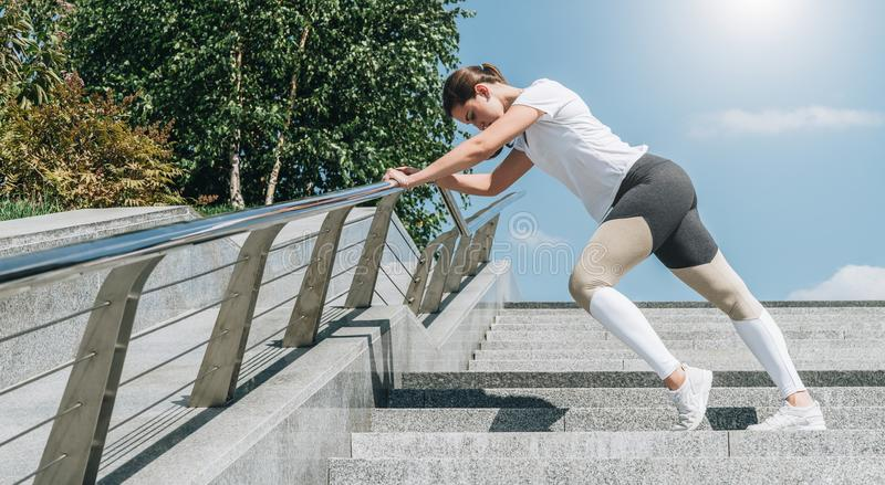 Sunny summer day. Young woman doing stretching exercises outdoor. Girl doing warm-up on steps before training. Workout. royalty free stock images