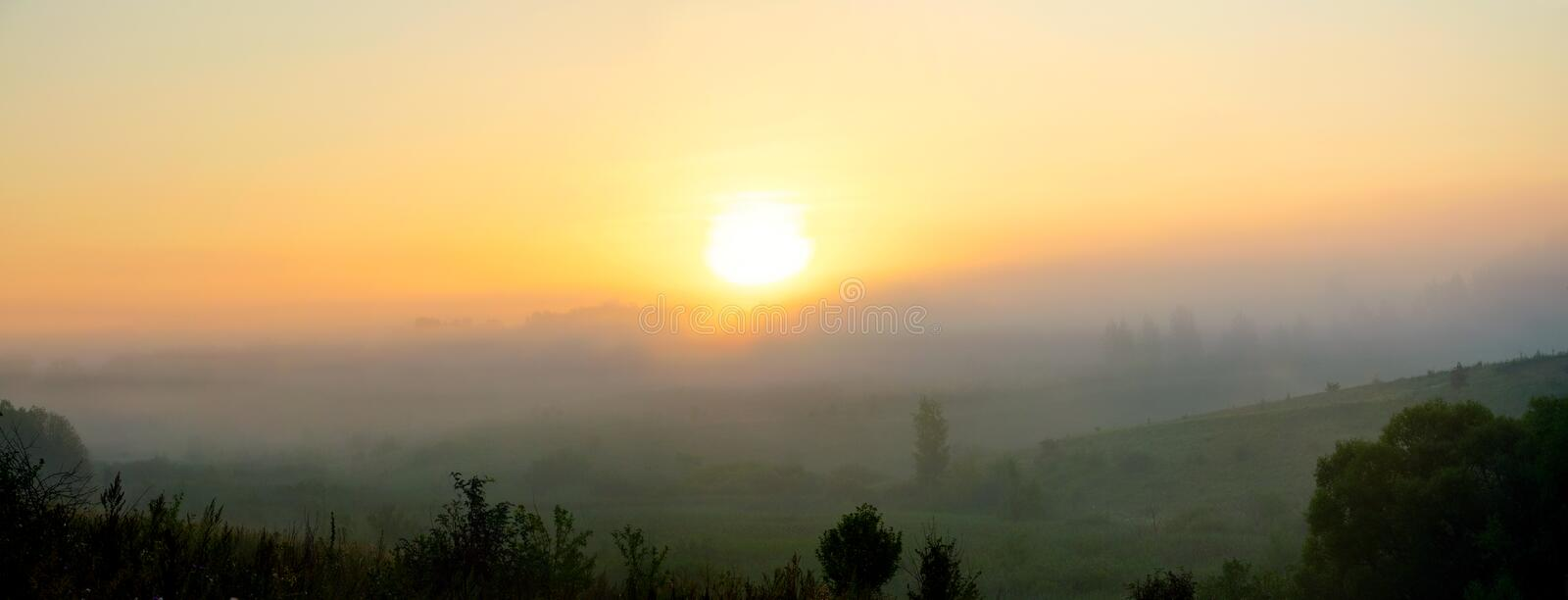 Sunny summer landscape with green hills covered by morning fog. Beautiful foggy scene with rising sun stock image