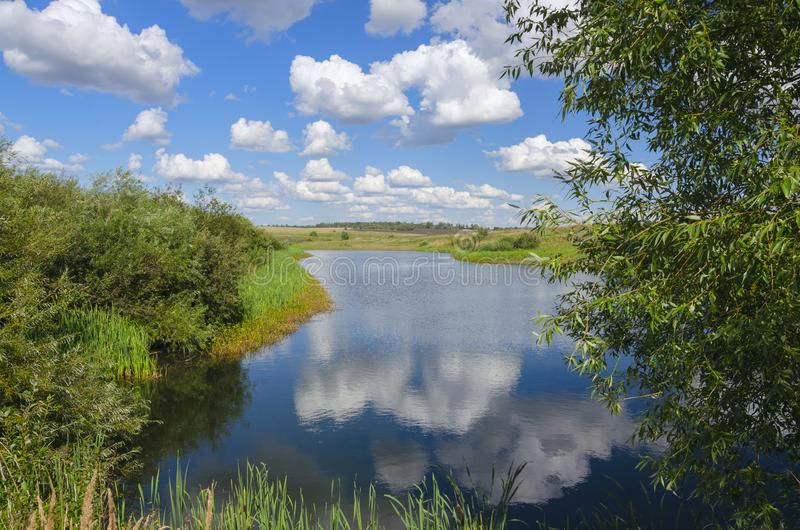 Sunny summer landscape with river,fields,green hills and beautiful clouds in blue sky. stock photo