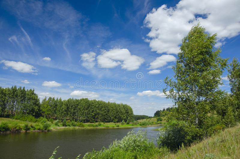 Sunny summer landscape with river,fields,green hills and beautiful clouds in blue sky. stock images