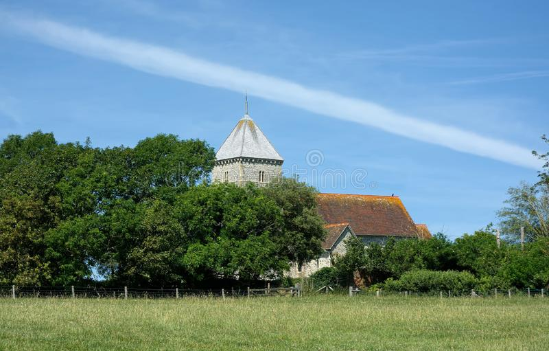 View across fields to St Andrews Church, Bishopstone. East Sussex. UK. Sunny summers day view across to St Andrews Church from the fields surrounding Bishopstone royalty free stock photos