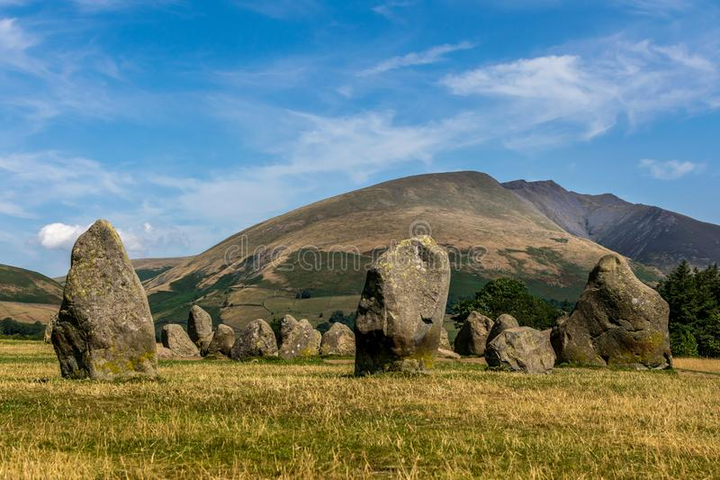 Ancient stone circle at castlerigg, with a mountain. A sunny summers day with a view of the stone circles from a bygone age. white fluffy clouds in the sky. a stock photography