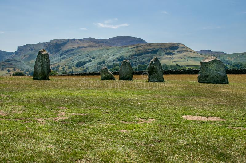 Ancient stone circle at castlerigg, with a mountain. A sunny summers day with a view of the stone circles from a bygone age. white fluffy clouds in the sky. a stock photo