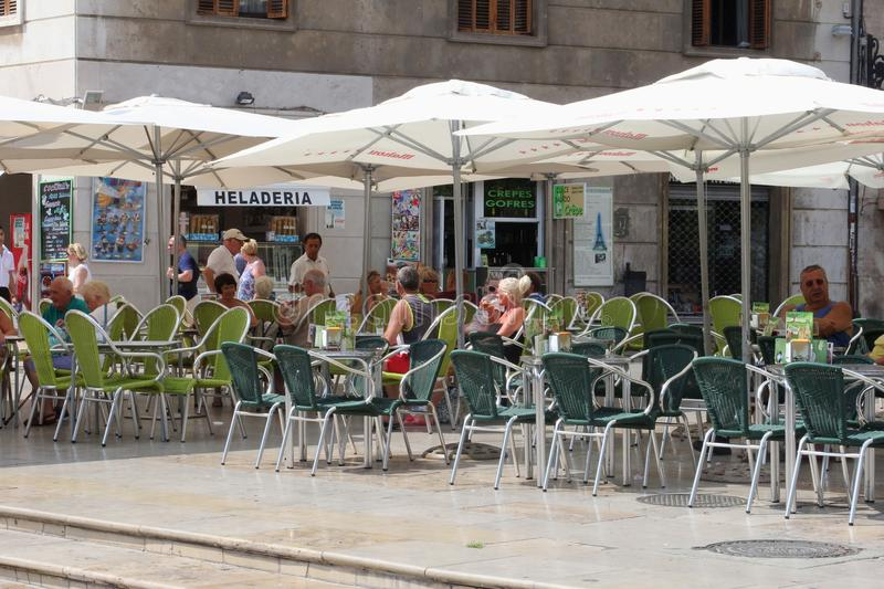 People sunny terrace, Valencia, Spain. People enjoy at a sunny terrace at the Plaza de la Virgen in the city centre of Valencia, Spain royalty free stock photography
