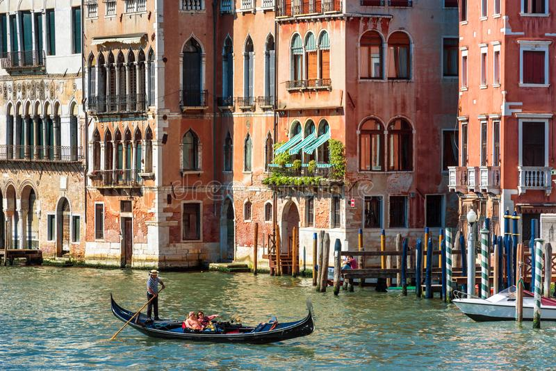 Sunny view of old street in Venice. Gondola with tourists sails on Grand Canal stock photos
