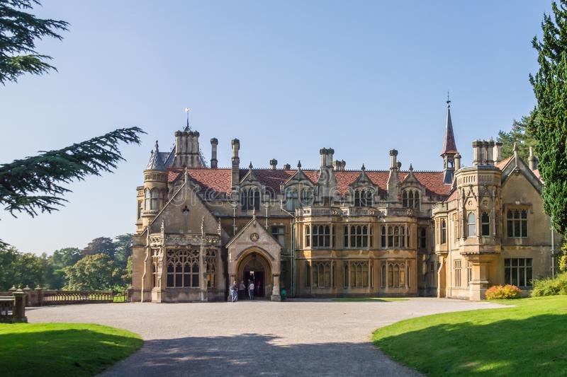 Sunny view of Tyntesfield manor house in Somerset. Tyntesfield manor house in Somerset lit from the side by autumn sunlight with a glimpse of the grounds stock photo