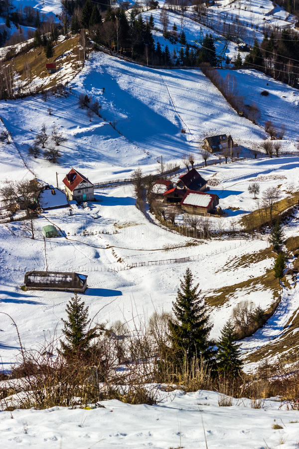 Sunny winter alpine scenery with small Romanian village in the valley of Bucegi stock images
