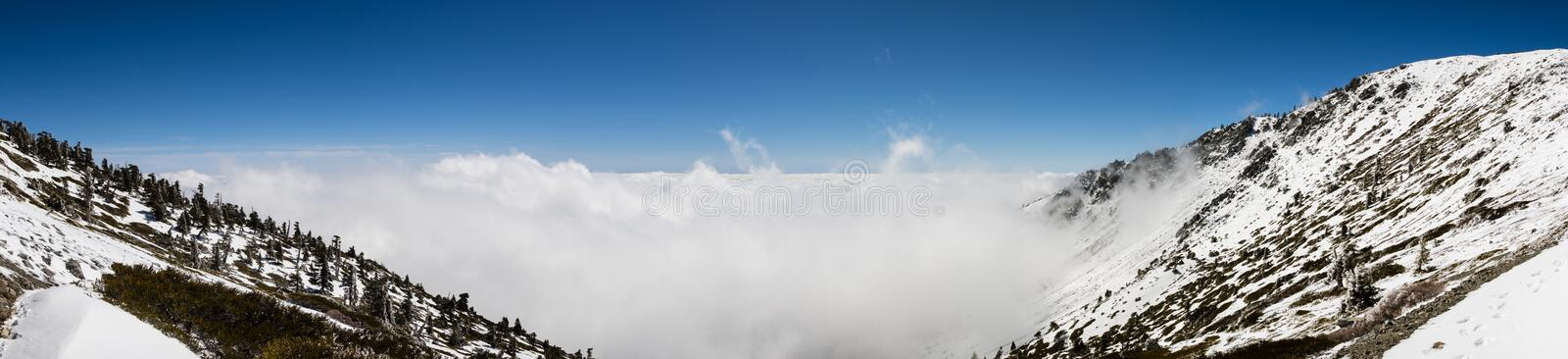 Sunny winter day with fallen snow and a sea of white clouds on the trail to Mt San Antonio (Mt Baldy), Los Angeles county, royalty free stock image