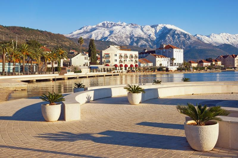 Sunny winter day. Montenegro, view of embankment of Tivat city and snowy peaks of Lovcen mountains stock photos
