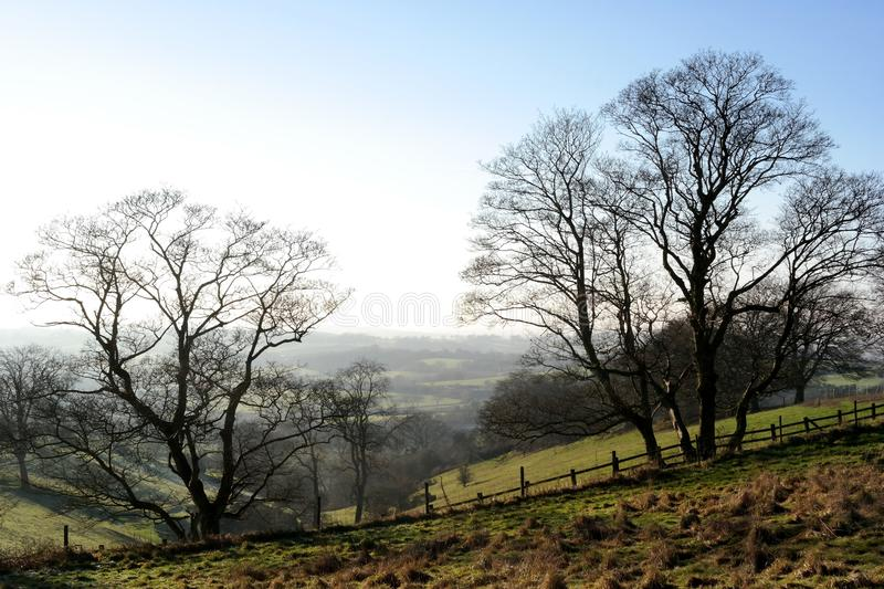 Sunny winter landscape. Hilly landscape with hazy distant countryside views blue sky sunny trees fenced stock photo