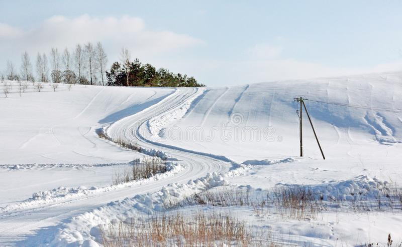 Sunny Winter Landscape met een Weg die op een Heuvel gaat royalty-vrije stock foto