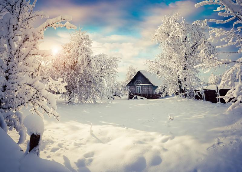 Sunny winter morning in the mountain village after heavy snowfall. Beautiful outdoor scene, Happy New Year celebration concept. Artistic style post processed stock image
