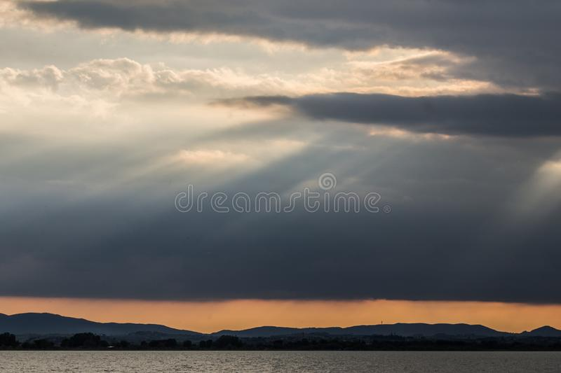 Sunrays at near sunset, with dark clouds in the background, an orange sky, and Trasimeno lake Umbria, Italy below stock photos