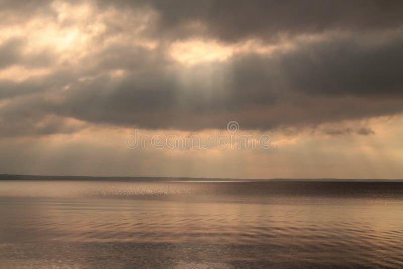 Sunrays przez chmur nad spokojnym jeziorem przed deszczem fotografia stock