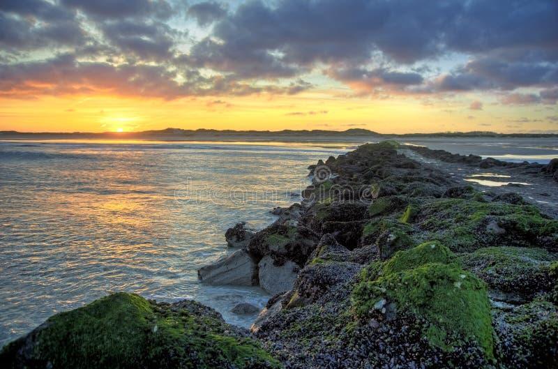 Sunrise over an ocean breakwater royalty free stock image