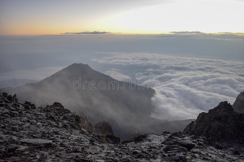 Trekking Mount Meru, Arusha National Park,. Sunrise above the clouds at the summit of Mount Meru, Arusha National Park, Tanzania royalty free stock photo