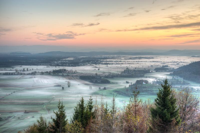 Sunrise above fields covered with morning mists royalty free stock photos
