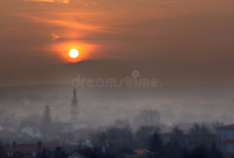 Sunrise above misty town royalty free stock images