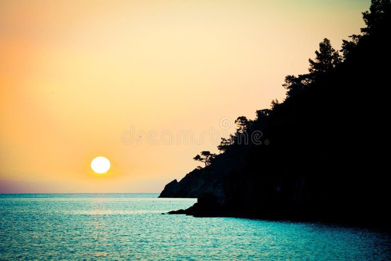 Sunrise above the sea silhouette of coast. Summer time sunrise above the sea orange colour stock image