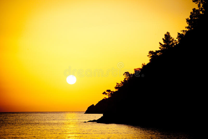 Sunrise above the sea silhouette of coast. Summer time sunrise above the sea yellow colour stock photography