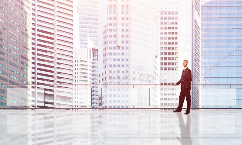 Sunrise above skyscrapers and businessman facing new day stock images