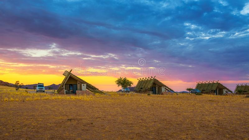 Sunrise above small chalets of a desert lodge near Sossusvlei in Namibia. Sunrise above small chalets of a desert lodge near the Namib-Naukluft National Park stock photography