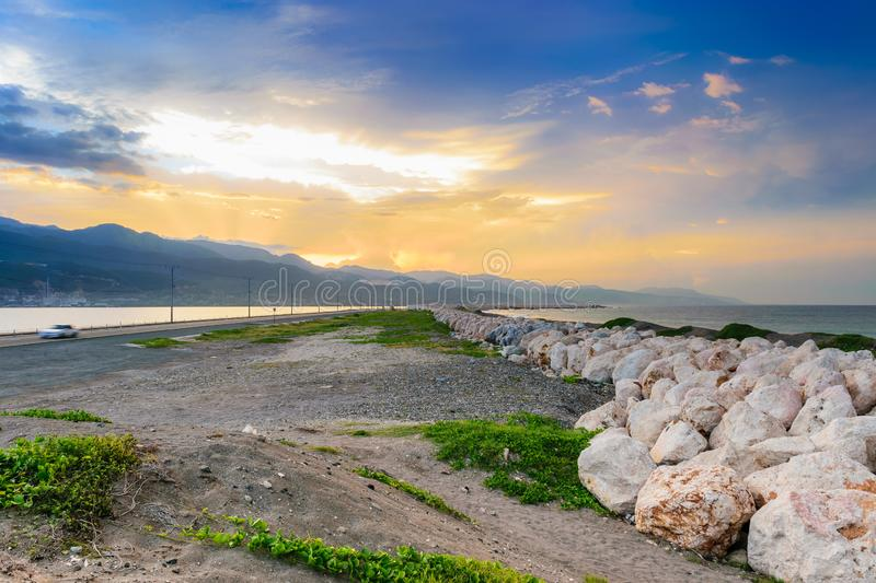 The Palisadoes peninsula in Kingston, Jamaica. Sunrise along the Palisadoes peninsula in Kingston, Jamaica with large rock boulders to help prevent flooding on royalty free stock photo