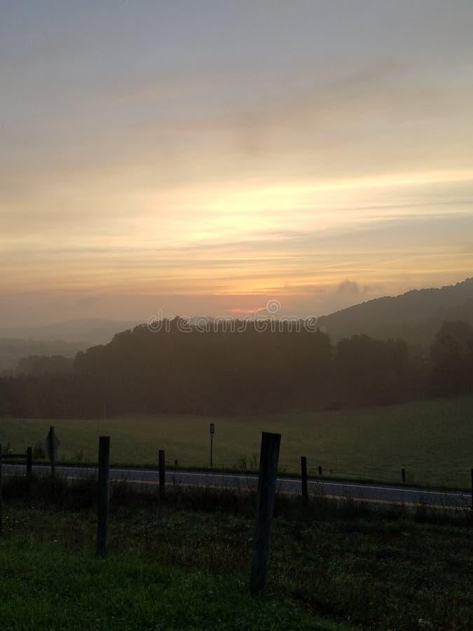 Sunrise as fog is lifting royalty free stock photo
