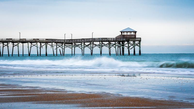 Sunrise at the Atlantic Beach Pier on Emerald Isle. Sunrise with the Atlantic Beach pier in the background with sand, ocean, waves and blue clouds royalty free stock photos