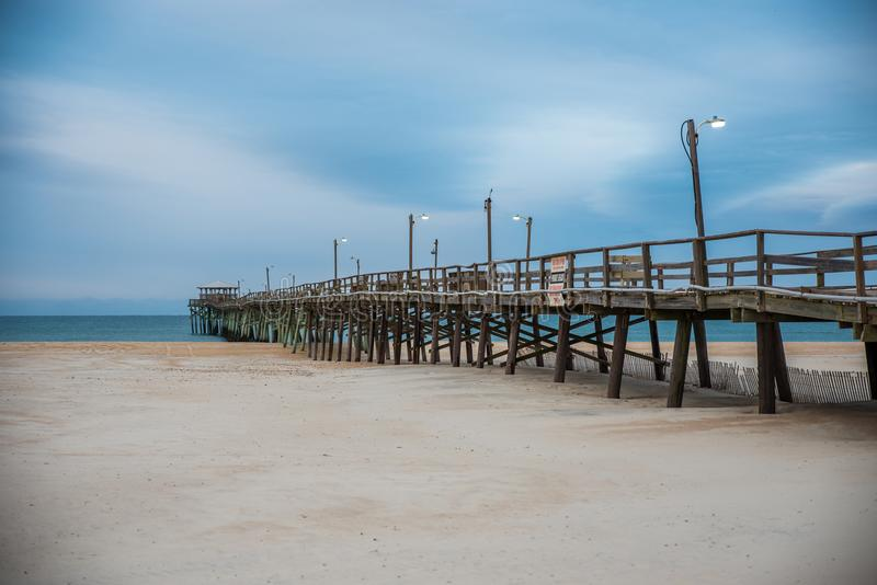 Sunrise at the Atlantic Beach Pier on Emerald Isle. Sunrise with the Atlantic Beach pier in the background with sand, ocean, waves and blue clouds stock photo