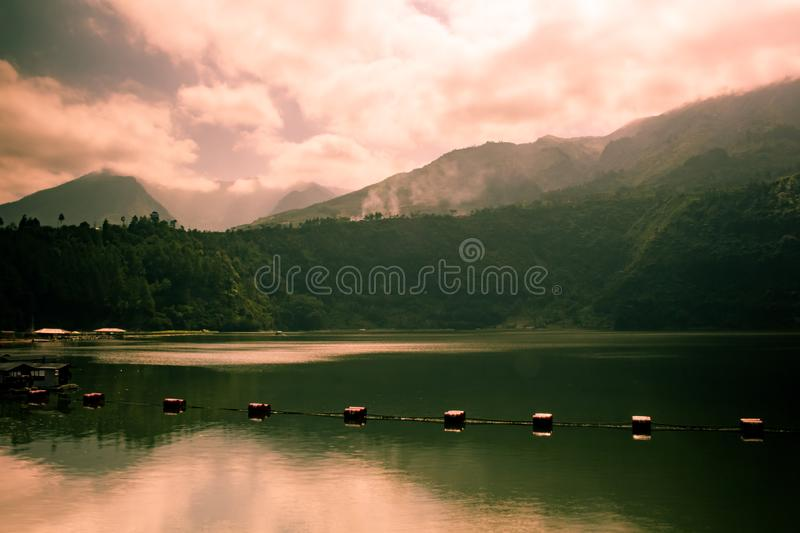 Sunrise from the back of mountain with dramatic clouds and peaceful lake stock photo