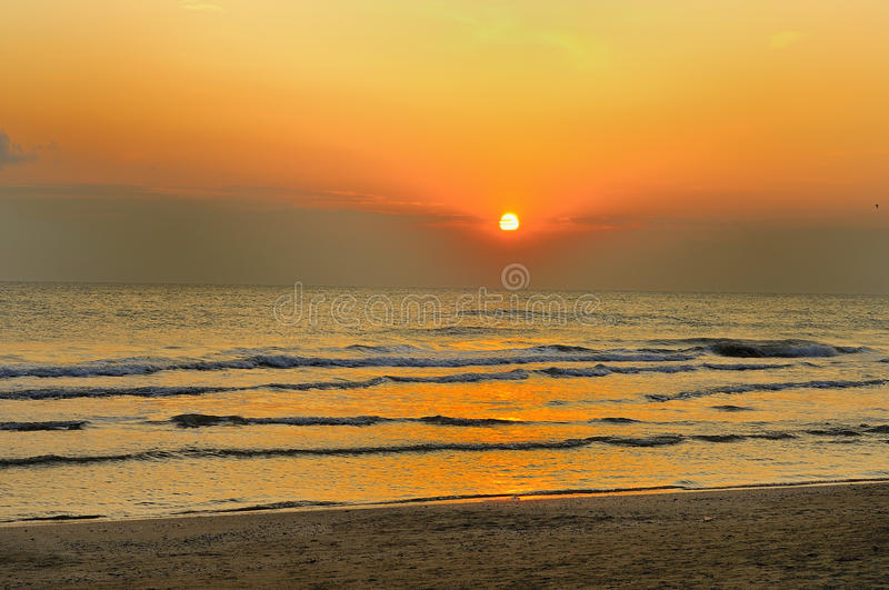 Sunrise on the beach. With waves stock photography