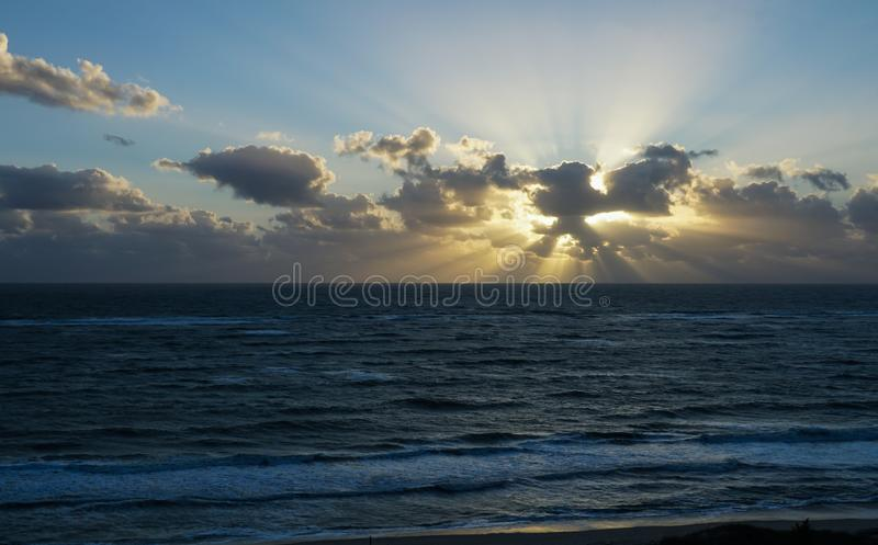 Sunrise on a beach with rays stock photography