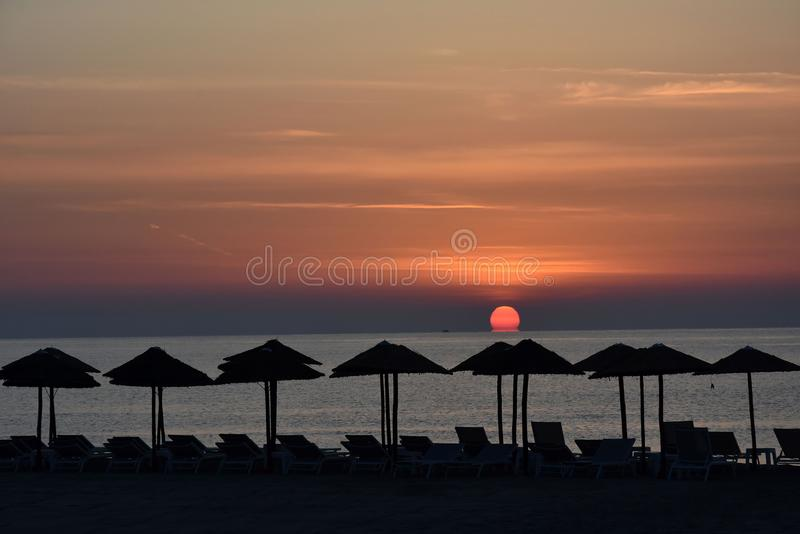 Sunrise at a beach in Katerini , greece. Early morning sunrise at a beach in Katerini, greece. In the foreground straw parasols and beach loungers royalty free stock photos