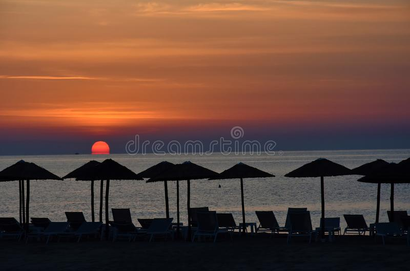 Sunrise at a beach in Katerini , greece. Early morning sunrise at a beach in Katerini, greece. In the foreground straw parasols and beach loungers royalty free stock image