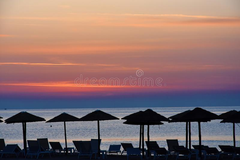 Sunrise at a beach in Katerini , greece. Early morning sunrise at a beach in Katerini, greece. In the foreground straw parasols and beach loungers royalty free stock photo
