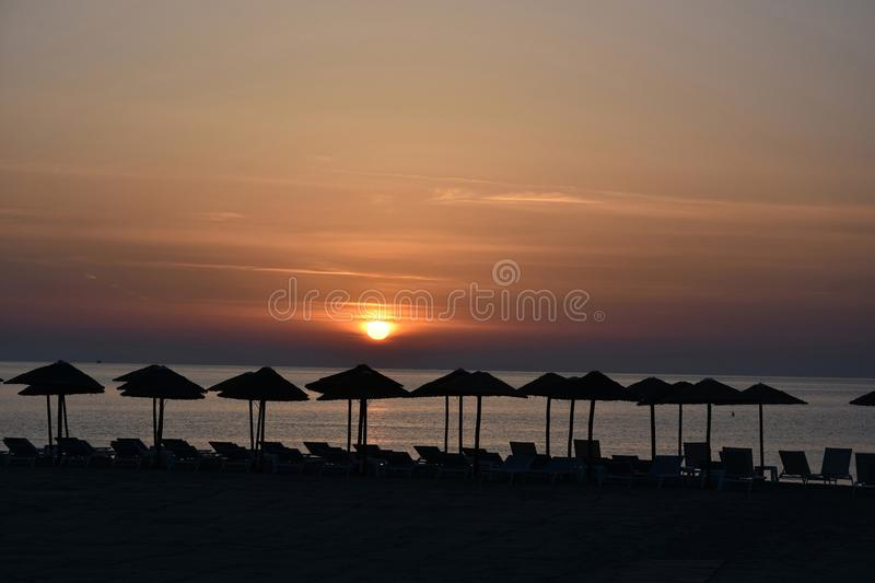 Sunrise at a beach in Katerini , greece. Early morning sunrise at a beach in Katerini, greece. In the foreground straw parasols and beach loungers stock photography